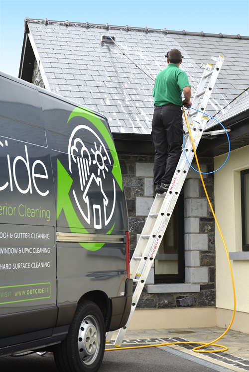 Roof cleaning with OutCide's pole and brush system.